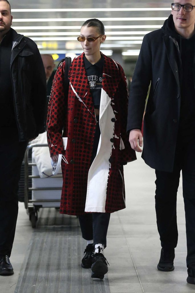 Bella Hadid Wears in a Red Checkered PVC Coat at Milan Airport in Milan-1