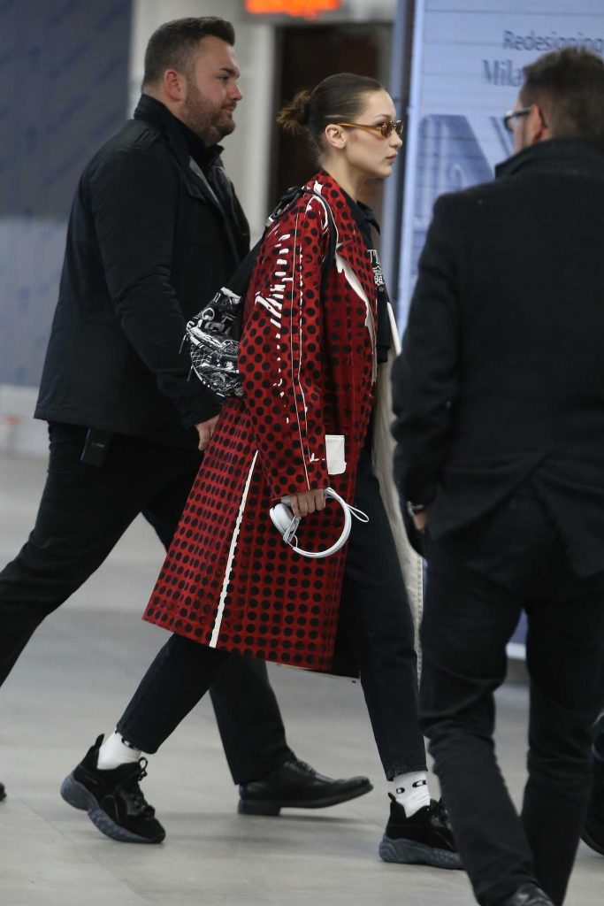 Bella Hadid Wears in a Red Checkered PVC Coat at Milan Airport in Milan-4