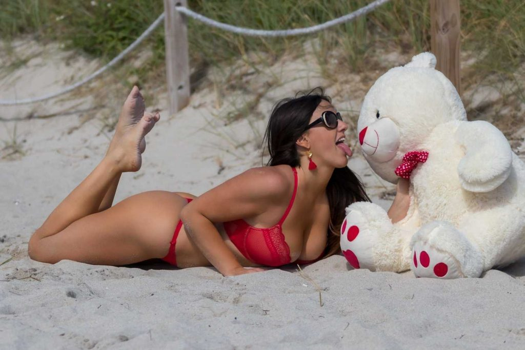 Claudia Romani in a Red Bikini Plays with a Teddy Bear at the Beach in Miami-3