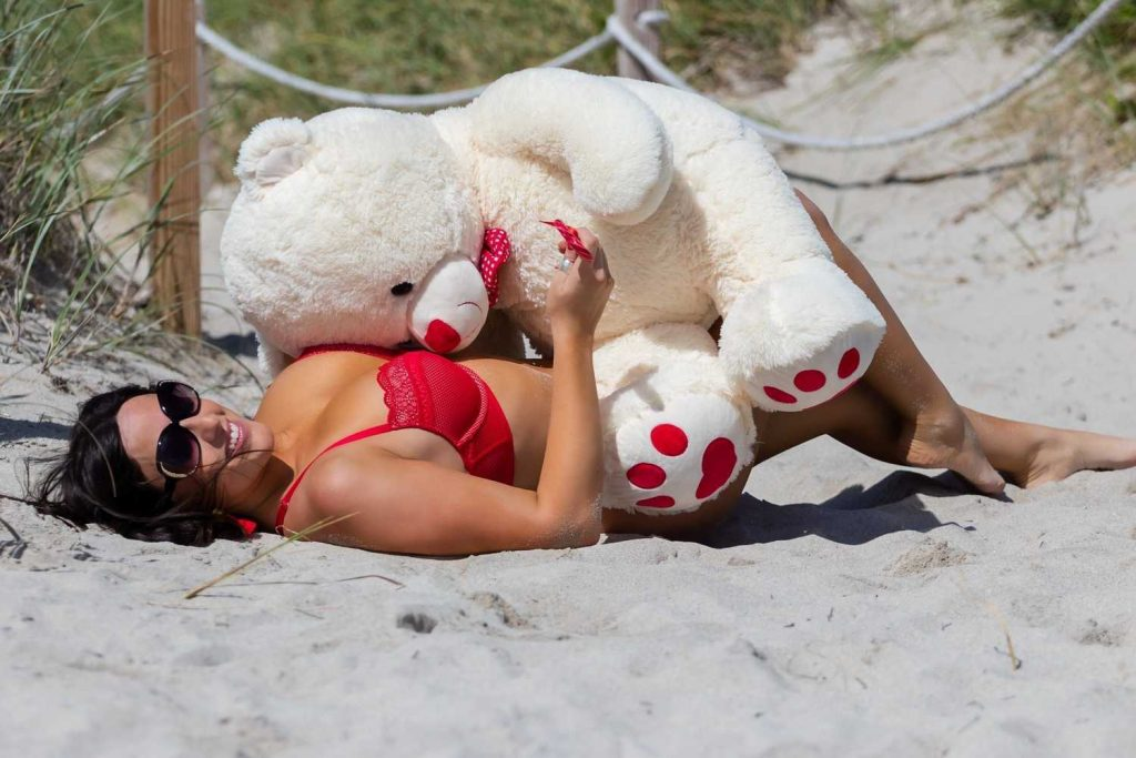 Claudia Romani in a Red Bikini Plays with a Teddy Bear at the Beach in Miami-5
