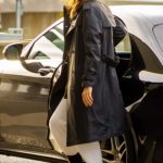 Irina Shayk in a Black Trench Coat Arrives at Heathrow Airport in London