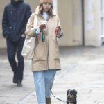 Emilia Clarke in a Beige Knit Hat Waslks Her Dog in London
