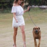Lizzie Cundy in a White Dress Walks Her Dog at a Park in London