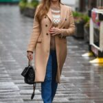 Kelly Brook in a Beige Coat Arrives at the Heart Radio in London