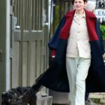 Emma Corrin in a Blue Coat Walks Her Dog Out with a Friend in London