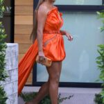 Chrissy Teigen in an Orange Dress Heads Out for a Party in Los Angeles